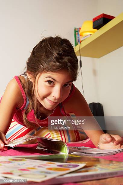 Girl (10-12) lying on bed with books, smiling, portrait