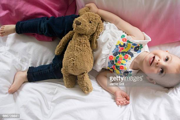 girl (18-23 months) lying on bed with teddy bear - 18 23 meses fotografías e imágenes de stock
