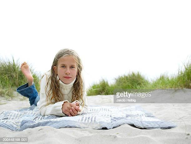 Girl (9-11) lying on blanket on beach, portrait