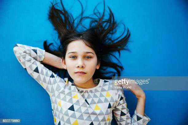 girl lying on blue background, looking at camera - kind vor der pubertät stock-fotos und bilder