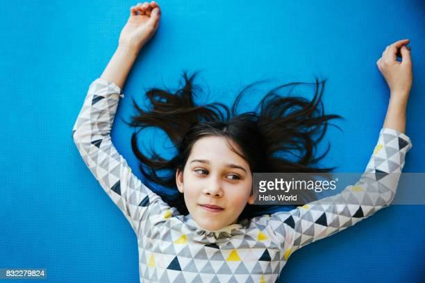 Girl lying on blue background