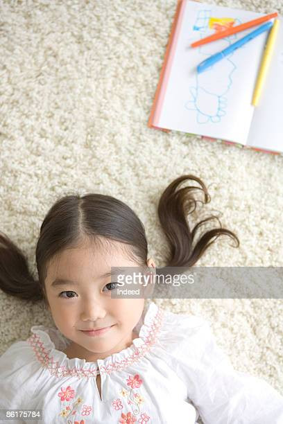 Girl lying on carpet, portrait
