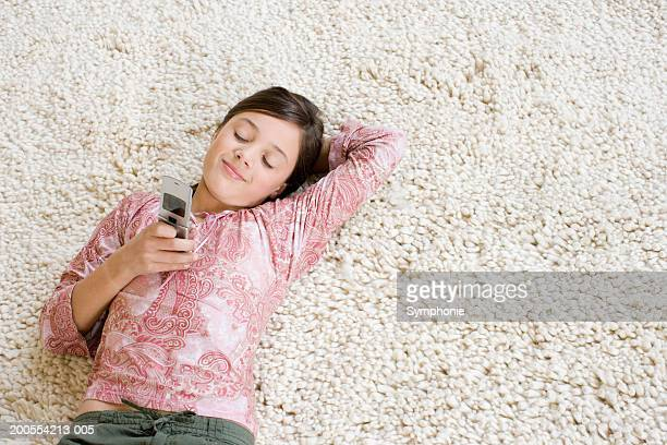 Girl (10-11) lying on carpet using mobile phone, elevated view