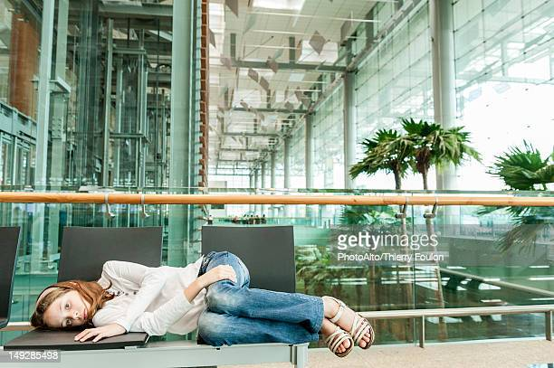 Girl lying on chairs in airport