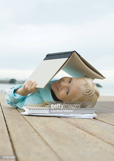 Girl lying on dock with book over head