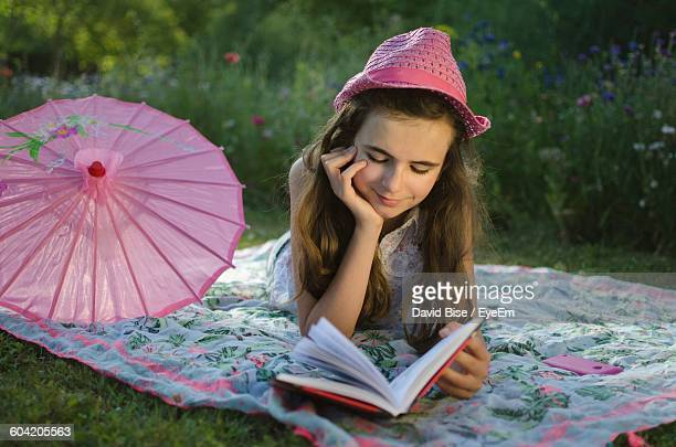 Girl Lying On Fabric And Reading Book At Grassy Field