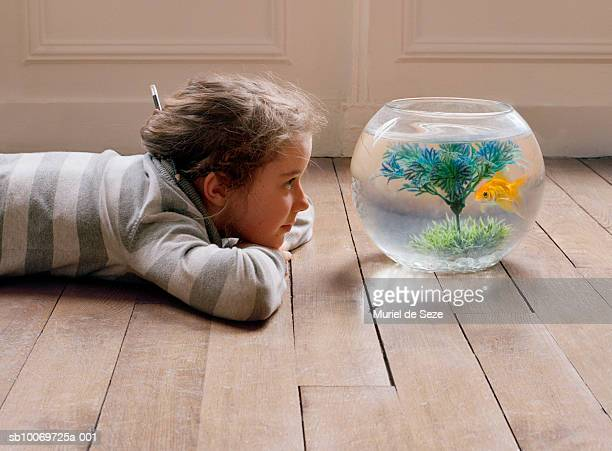 Girl (10-11) lying on floor and watching goldfish in bowl