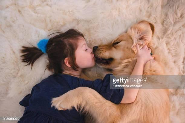 girl lying on floor kissing her golden retriever dog - golden retriever photos et images de collection