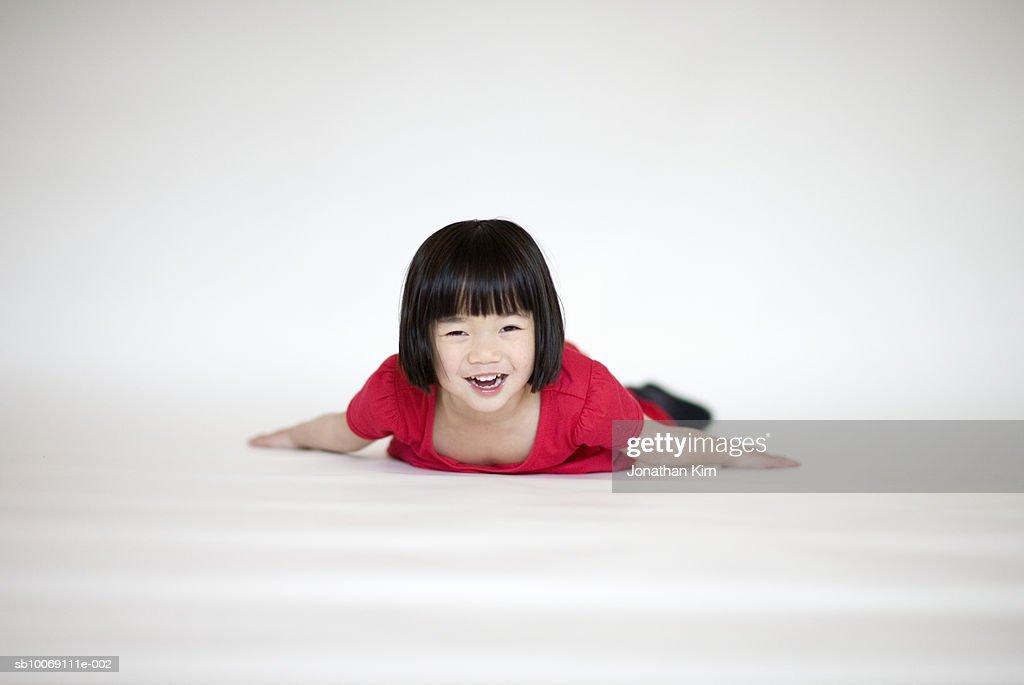 Girl lying on floor, smiling, portrait : Stockfoto