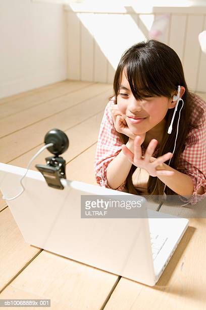 girl lying on floor, wearing headset and looking into laptop webcam - very young webcam girls stock photos and pictures
