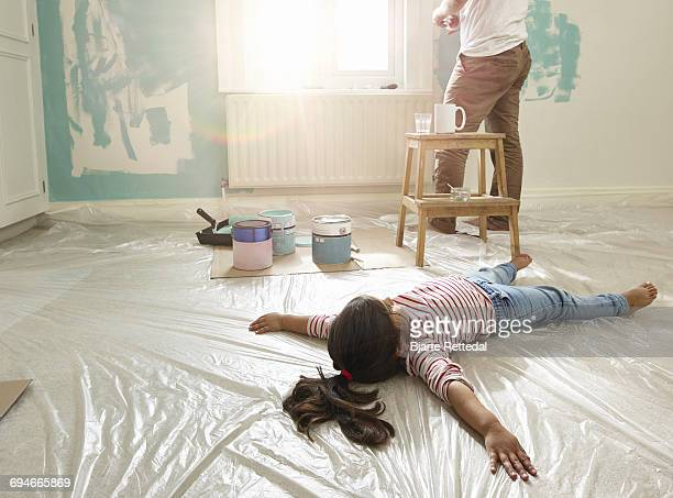 Girl lying on floor while dad decorates room