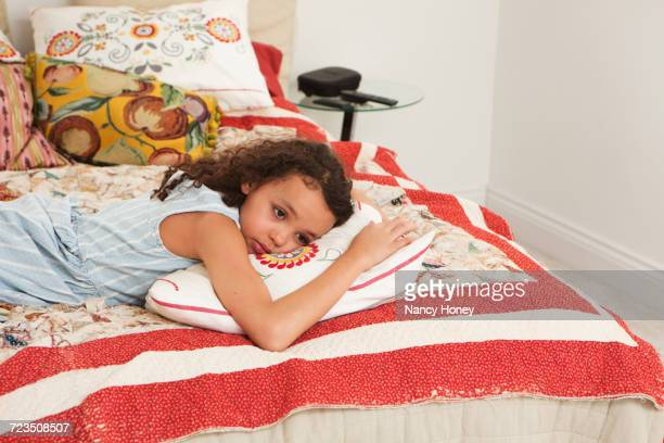 Girl lying on front on bed
