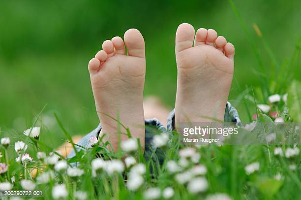 girl (3-5) lying on grass, close-up of feet - gras stock pictures, royalty-free photos & images