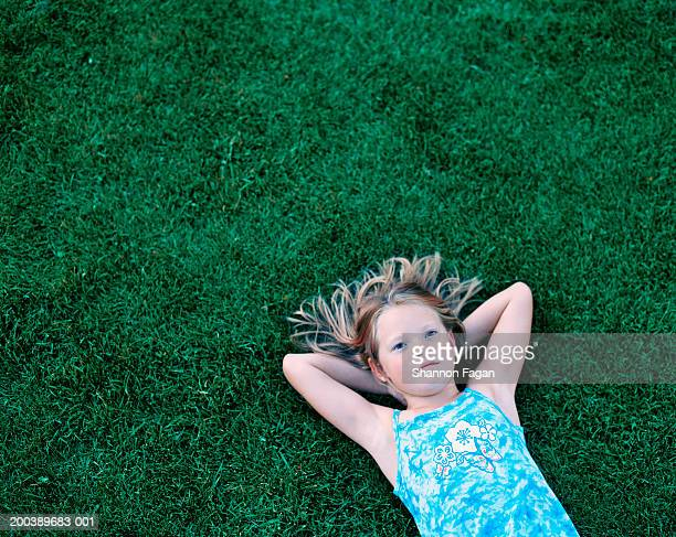 Girl (7-9) lying on grass, elevated view