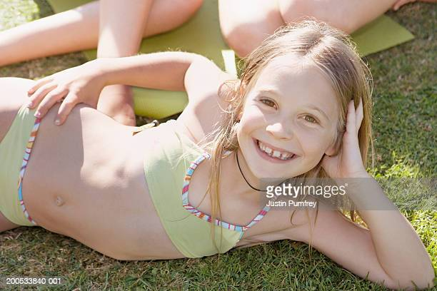 Girl (10-12) lying on grass in bikini smiling, portrait