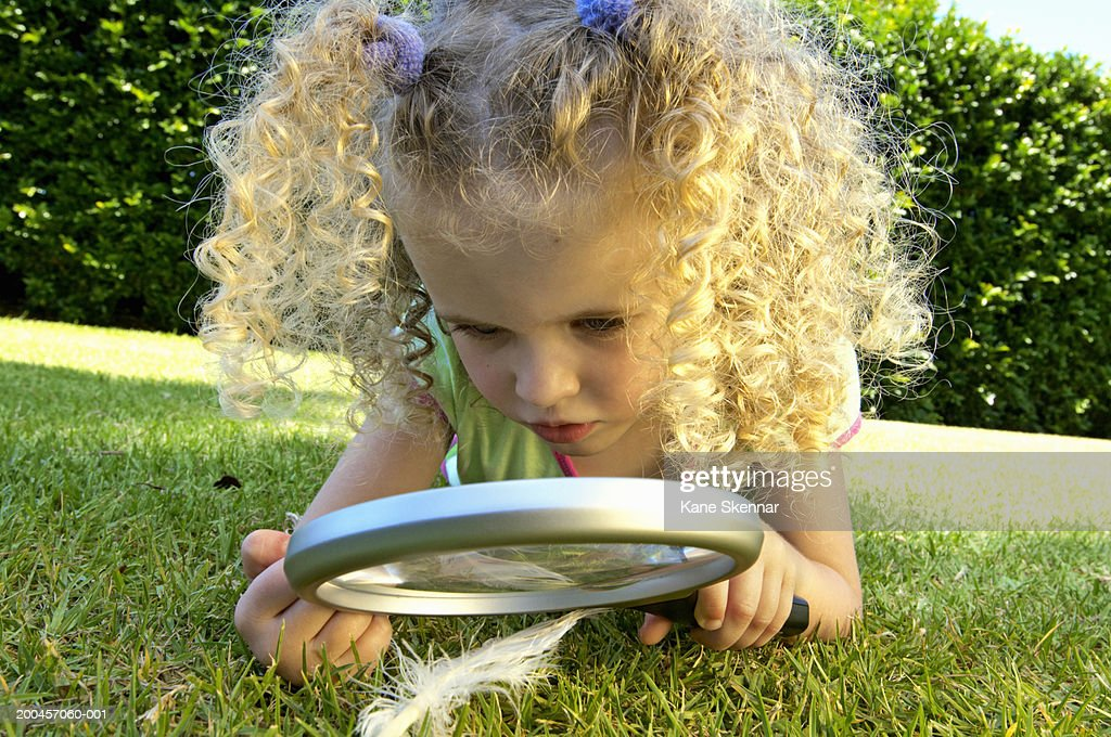 Girl (3-5) lying on grass, looking at feather through magnifying glass : Stock Photo