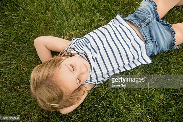 girl (2-3) lying on grass - hände hinter dem kopf stock-fotos und bilder