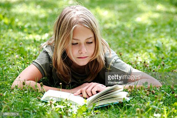 Girl (10-11) lying on grass reading, smiling