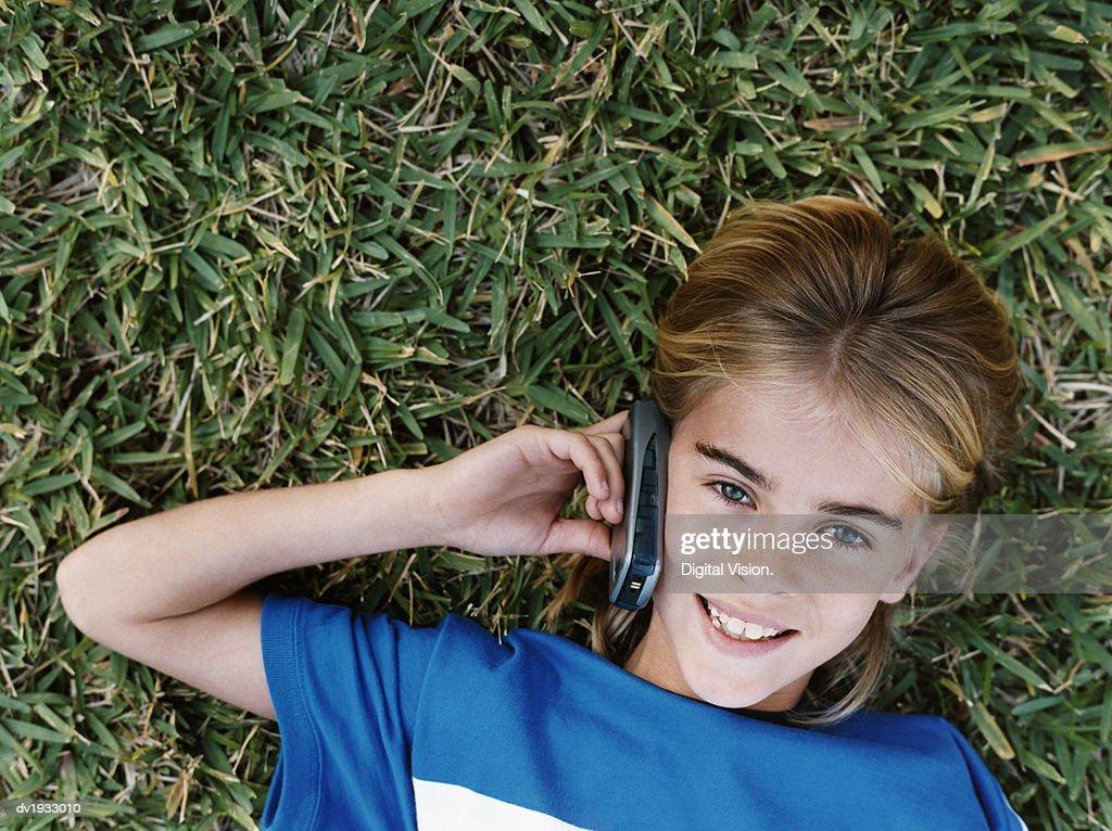 Girl Lying on Grass Using Mobile Phone : Stock Photo
