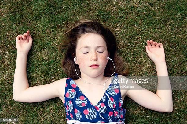 Girl lying on grass with earphones