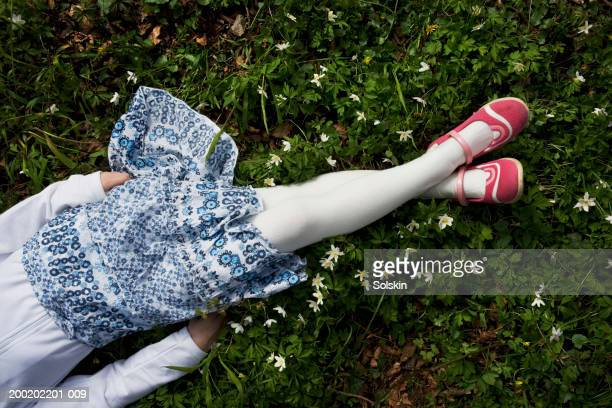 girl (8-10) lying on grass with hands by sides, overhead view - little girls undies stock pictures, royalty-free photos & images