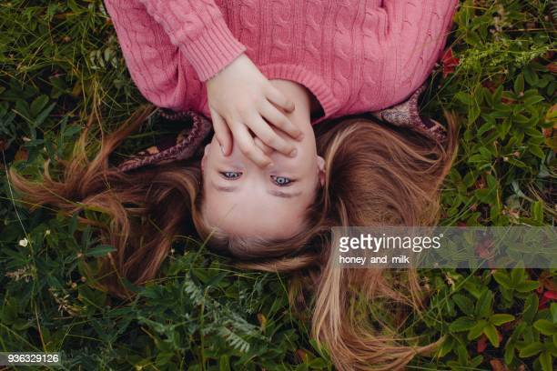 Girl lying on grass with her hand covering her mouth