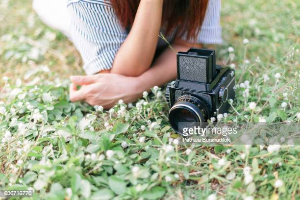 Girl lying on grasses with her vintage film camera