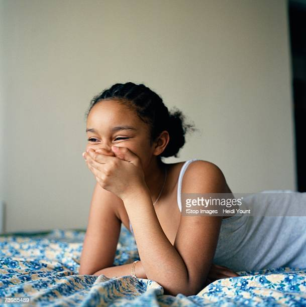 Girl lying on her bed laughing