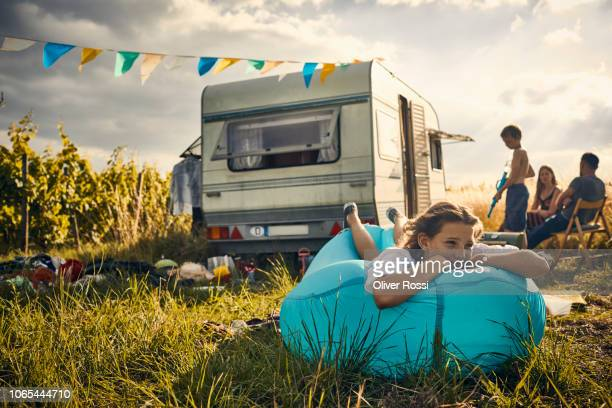 girl lying on inflatable lounger next to caravan in the countryside - camper trailer stock pictures, royalty-free photos & images