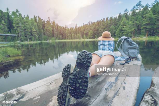 girl lying on lake pier, relaxing in nature - lake bottom stock photos and pictures