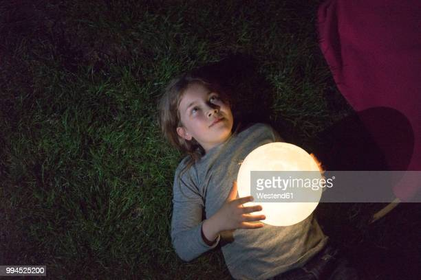 girl lying on meadow, holding moon - regarder photos et images de collection