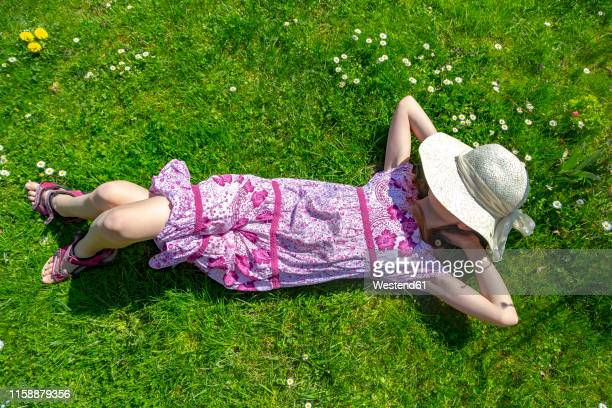 girl lying on meadow in garden - mädchen stock-fotos und bilder
