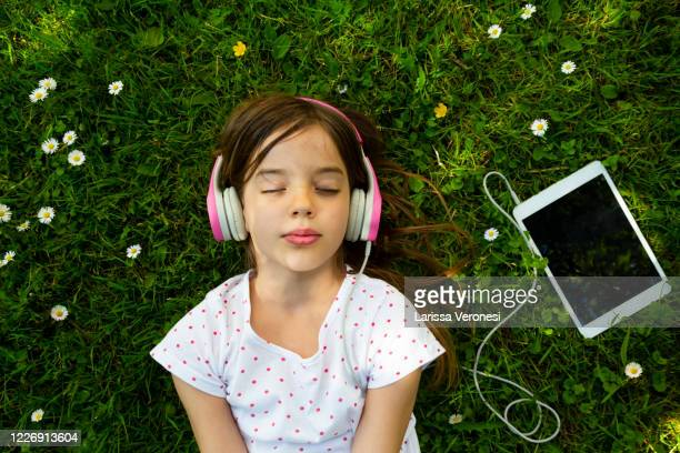 girl lying on meadow listening music with headphones - larissa veronesi stock-fotos und bilder