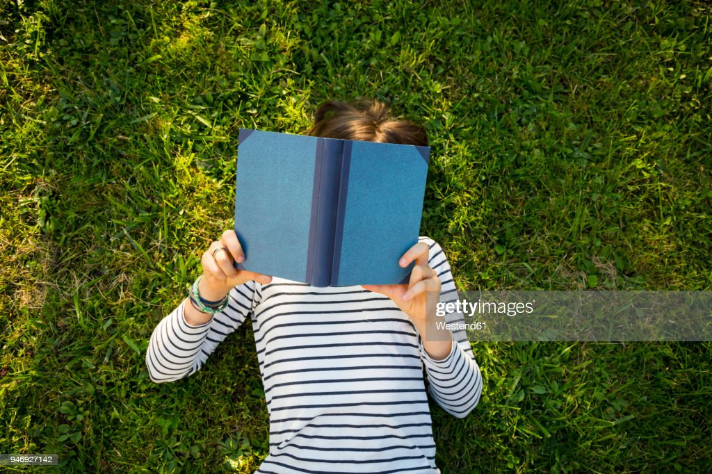 Girl lying on meadow reading a book : Foto de stock