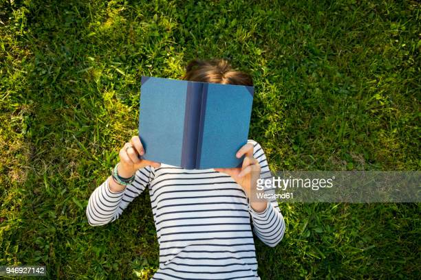 girl lying on meadow reading a book - reading stock pictures, royalty-free photos & images