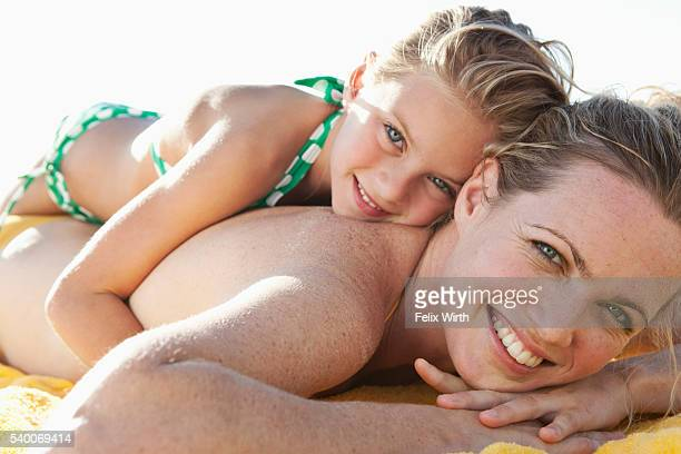 Girl (5-6) lying on mother on beach and looking at camera