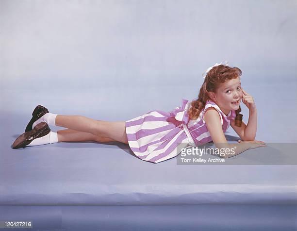 パープルの背景に横たわる少女の笑顔、ポートレート、