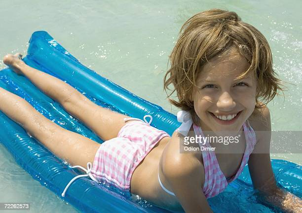 girl lying on raft - little girl laying on the beach stock photos and pictures