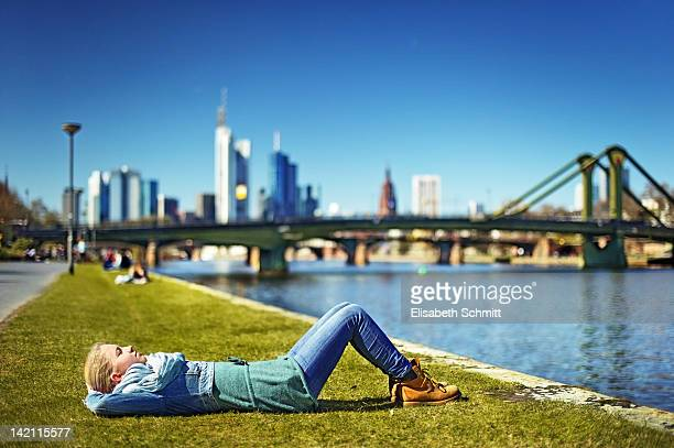 girl lying on riverbank - frankfurt stock-fotos und bilder