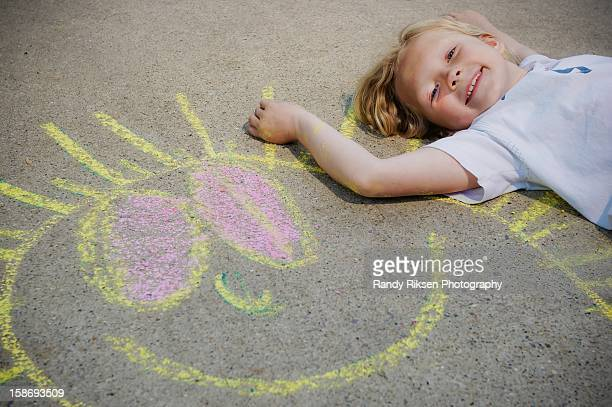 Girl lying on sidewalk with chalk art