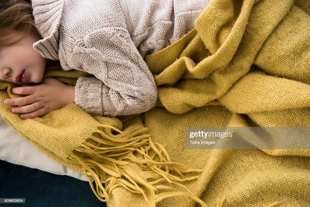 Girl (4-5) lying on sofa covered with blanket : Stock Photo