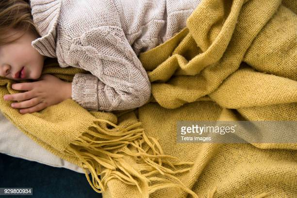girl (4-5) lying on sofa covered with blanket - cosy stock pictures, royalty-free photos & images