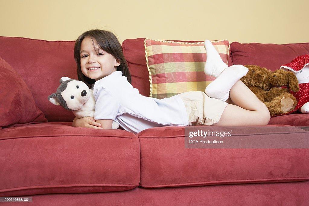 Girl (5-7) lying on sofa with stuffed animals, portrait : Stock Photo