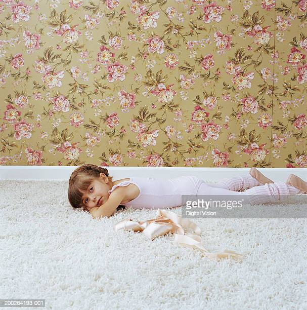 Girl (3-5) lying on stomach by ballet shoes, portrait, side view