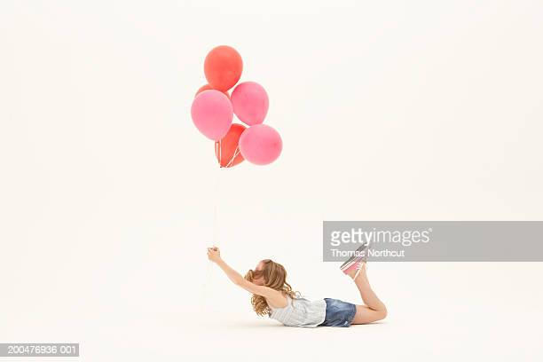 Girl (8-10) lying on stomach, holding bunch of balloons, side view