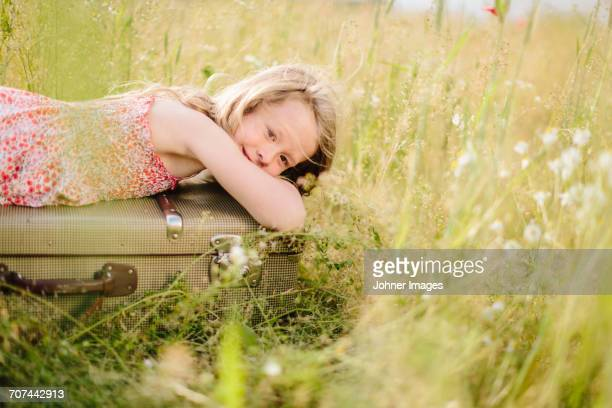 Girl lying on suitcase in meadow