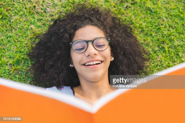 girl lying on the grass and reading a book - legge foto e immagini stock
