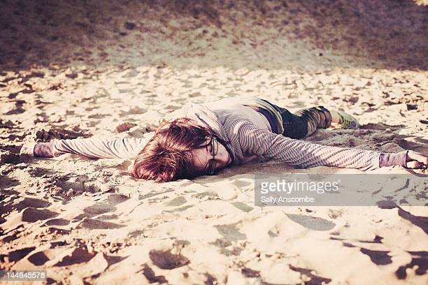 girl lying on the sand at the beach - lying on front stock pictures, royalty-free photos & images