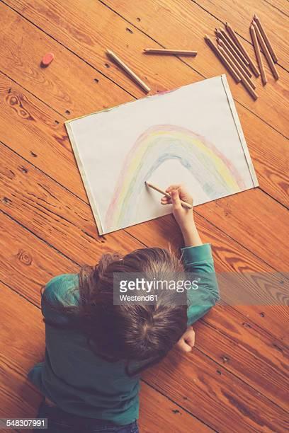 Girl lying on timber floor drawing rainbow
