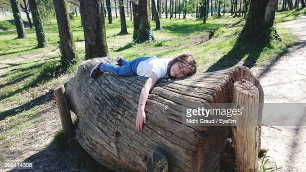 Girl Lying On Tree Trunk In Forest